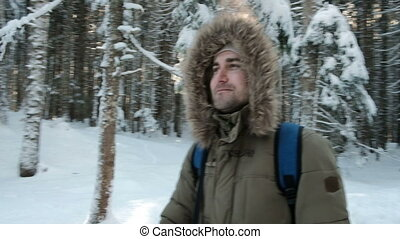 Young man walking in wintertime in pine forest outdoors. ...