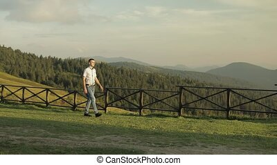 Young man walking neat fence in the park. Slow motion