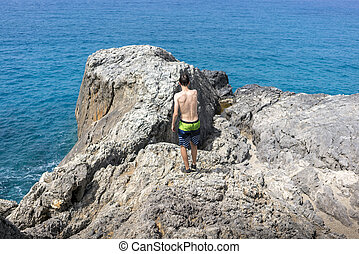 young man walking on a cliff