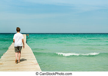 Young man walking on a long wood pier