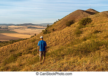 Young man walking on hill Rana and looking to Czech central mountain valley at sunrise