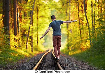Young man walking on the railway