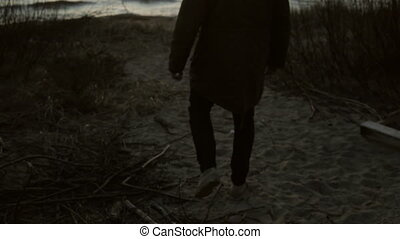 Young man walking on the sandy beach at the evening. Sad male spending time alone on the shore of the beach at sunset.