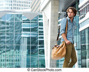 Young man walking outdoors with bag