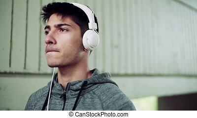 Young man walking with headphones in the city, listening to music.