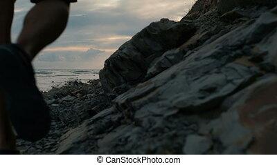 Young man walks along beach in late summer evening outdoors.