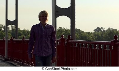 Young Man Walks Along The Handrails of a Bridge at Sunset in Slo-Mo