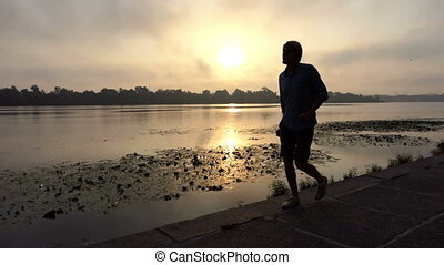 Young Man Walks Happily Along The Dnipro Riverbank at Sunset