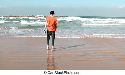 Young man walks on summer sea beach, throws stone. Freedom...