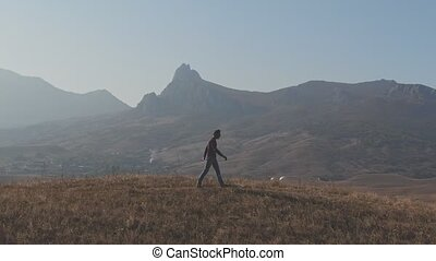 Young man walks on top of a hill and jumps for joy in the background of mountains