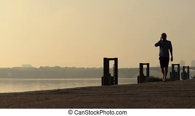 Young Man Walks While Speaking on His Mobile at the Dnipro at Sunset