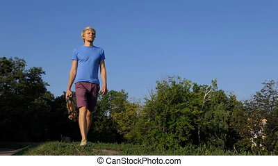 Young man walks with a lot of medals on a lake bank in summer