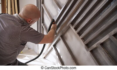 Young man washes metal shelves after repairing living room.