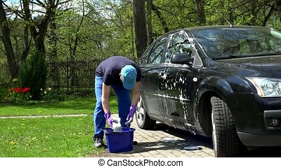 Young man washing his black car with soapy sponge.