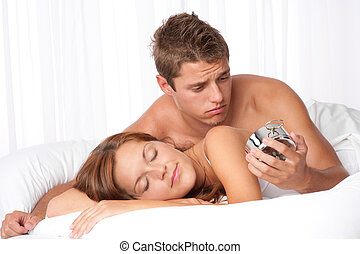 Young man watching alarm clock