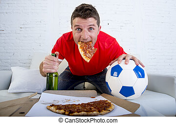 young man watching football game on television looking excited and anxious sitting on sofa