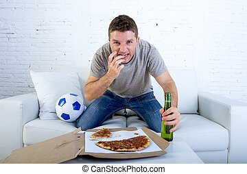 young man watching football game on television nervous and excited suffering stress biting fingernail on sofa