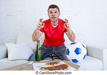 man watching football game on television nervous and excited suffering stress fingers crossed for goal