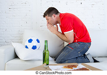 young man watching football game on television nervous and excited suffering stress praying god for goal
