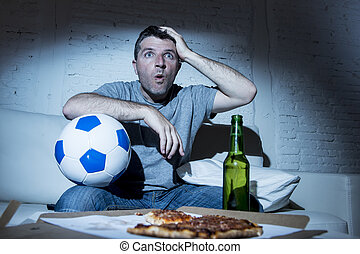 young man watching football game on tv nervous and excited suffering stress on couch