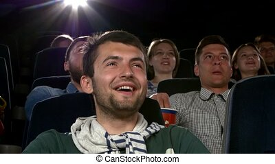 Young man watching movie at cinema: comedy. Close up