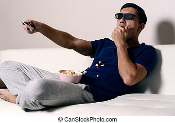 Young man watching movie in 3D glasses and eating popcorn