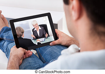 Young Man Watching Movie On Tablet Pc