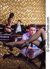 Young man watching sexy strip tease dancer with long beautiful legs dancing on the stage. Dancer with perfect body dancing on background