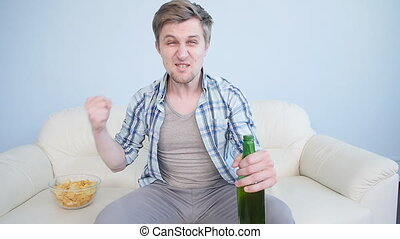 Young man watching sports on tv and supporting team at home