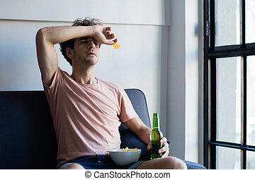 Young man watching tv on the couch.