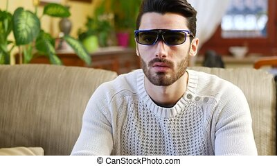 Young man wearing 3d glasses reacting in surprise and...