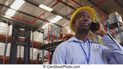 Young man wearing a hard hat using smartphone in a warehouse...