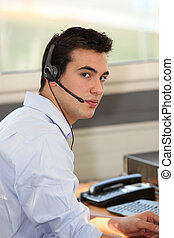 Young man wearing a headset in front of a computer