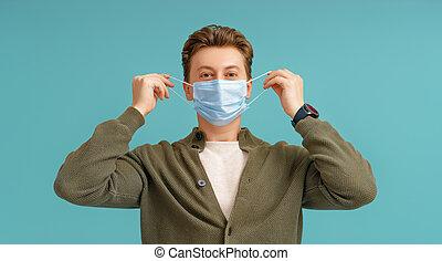 Young man wearing facemask during coronavirus and flu ...