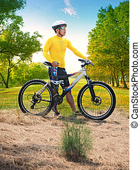 young man wearing rider suit with safety helmet and mountain...