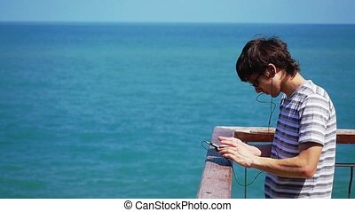 Young man wearing sunglasses and headphones listen to music...