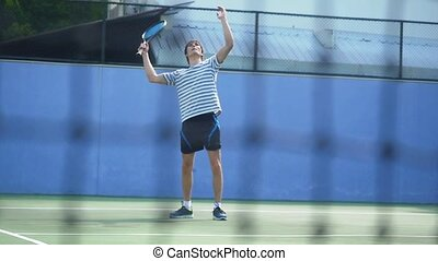 Young man wearing sunglasses playing Tennis with tennis racket on sunny day. slow motion.