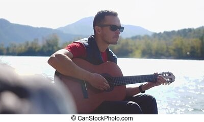 Young man wearing sunglasses plays on a guitar sitting by...