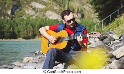 Young man wearing sunglasses plays on a guitar sings song sits by mountain river on sunny day. 3840x2160, 4k