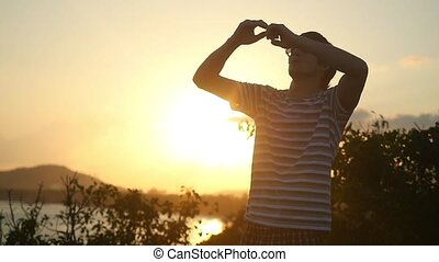 Young man wearing sunglasses raising arms at beautiful sunset stands on top of the mountain in slow motion.