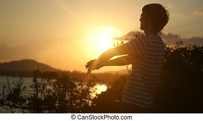 Young man wearing sunglasses raising arms to the rising sun at beautiful sunset on top of the mountain in Slow Motion.