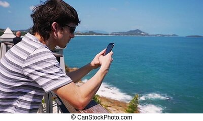 Young man wearing sunglasses sends messages with mobile phone stands by the sea. Slow motion.