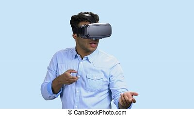Young man wearing virtual reality glasses. Enthusiastic man in VR glasses simulating shooting with virtual gun. Shooting VR game.
