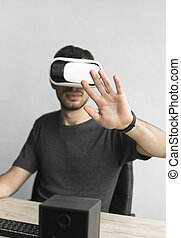 Young man wearing virtual reality goggles headset and sitting in the office against computer. Connection, technology, new generation. Man trying to touch objects or control VR with a hand.