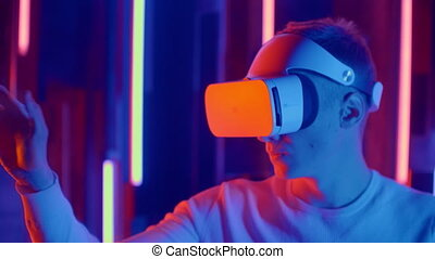 Young man Wearing Virtual Reality Headset Draws Abstract Lines. Creative Young Girl Does Concept Art with Augmented Reality