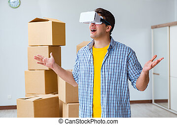 Young man wearing VR glasses moving in new apartment