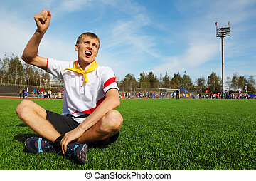 young man wearing white shirt sitting on football field and shouting and waving his hand