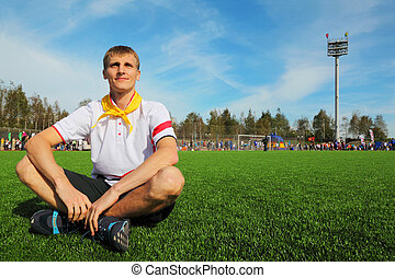 young man wearing white shirt sitting on football field and smiles