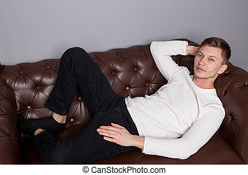 Young man wearing white sweater is lying on a leather sofa