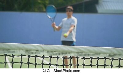 Young man wearng sunglasses playing Tennis with tennis racket on sunny day. slow motion blurred on grid foreground. 1920x1080, hd